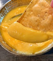 cheddar cheese sauce in bowl scooped with tortilla chip