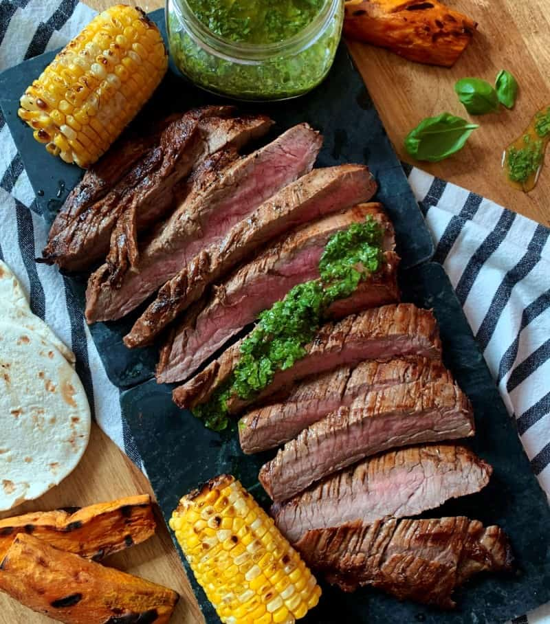 overhead view of medium rare sliced steak drizzled with bright green chimichurri