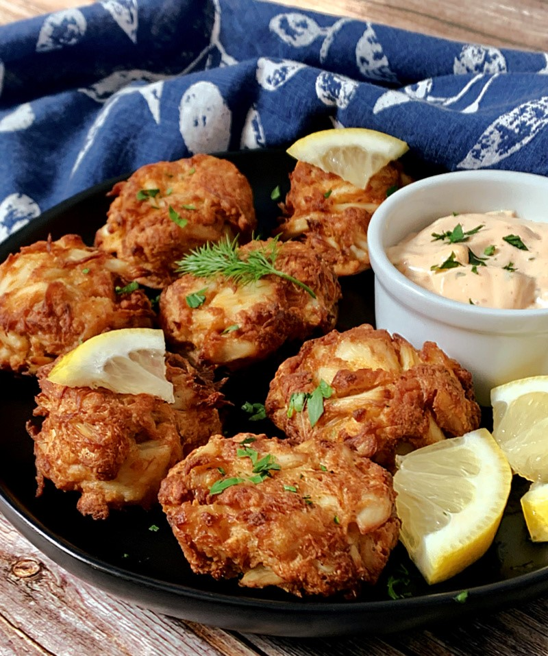 black plate with mini crab cakes and dipping sauce