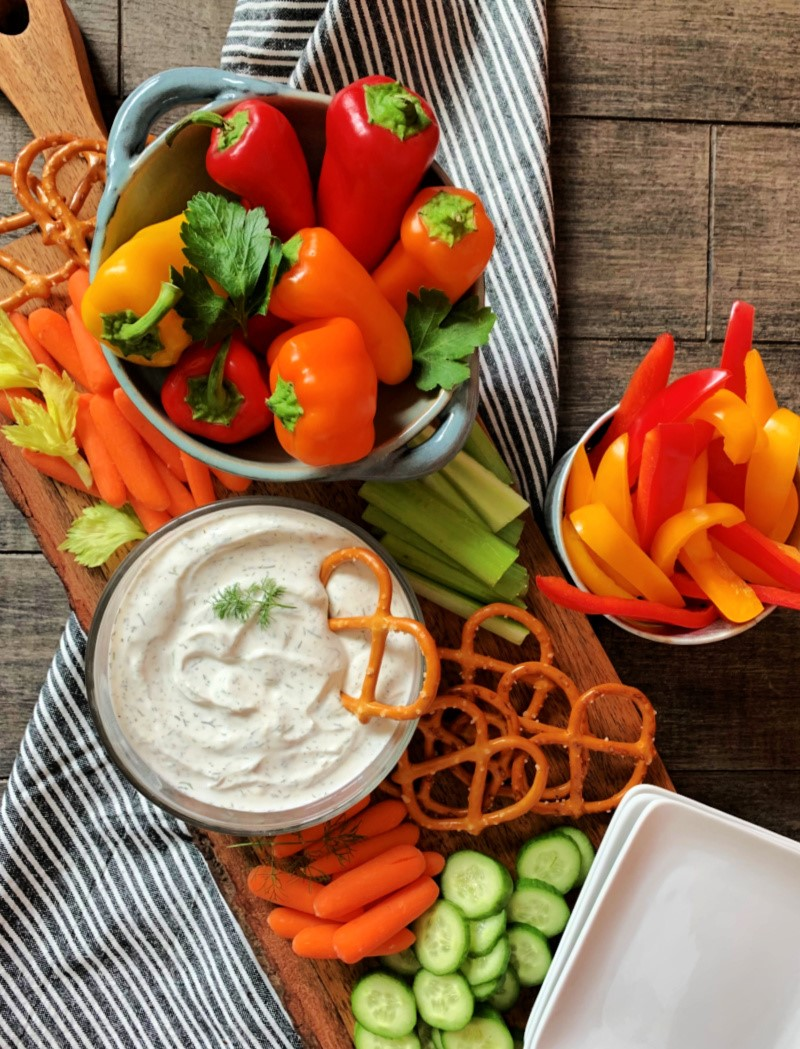 dill dip in clear bowl, mini bell peppers in another container