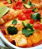 closeup of baked enchiladas in casserole dish topped with melted cheese