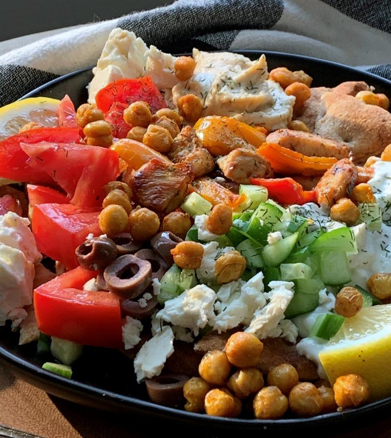 black plate piled high with greek nachos - pita, chicken,  hummus, tzatziki, veggies and chickpeas