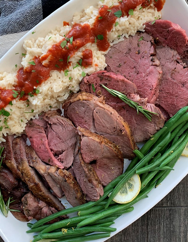 white platter with sliced lamb, green beans and white rice