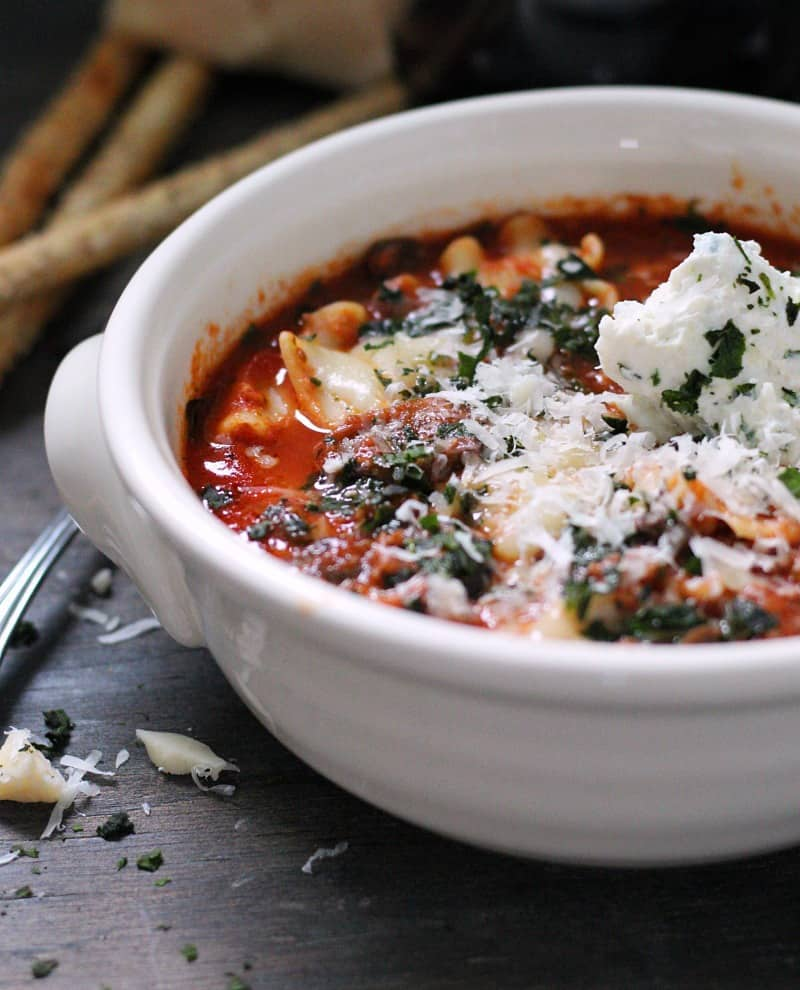 bowl of lasagna soup with a dollop of ricotta garnished with basil