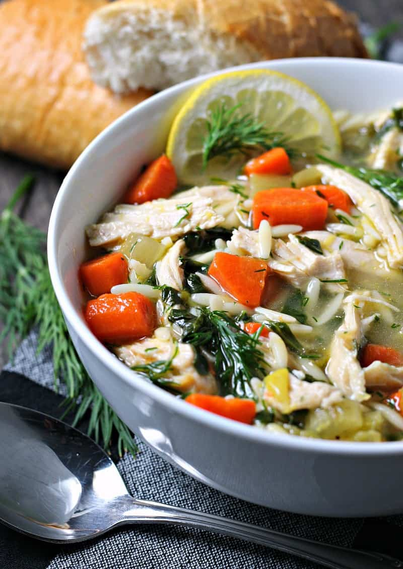 lemon chicken orzo soup ~ closeup of soup loaded with shredded chicken, carrots, orzo, fresh dill sprigs and a slice of lemon.