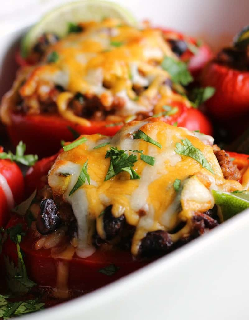 Mexican Stuffed Peppers ~ seasoned ground beef, rice and black beans topped with cheese and baked in colorful bell peppers and a bold enchilada sauce.