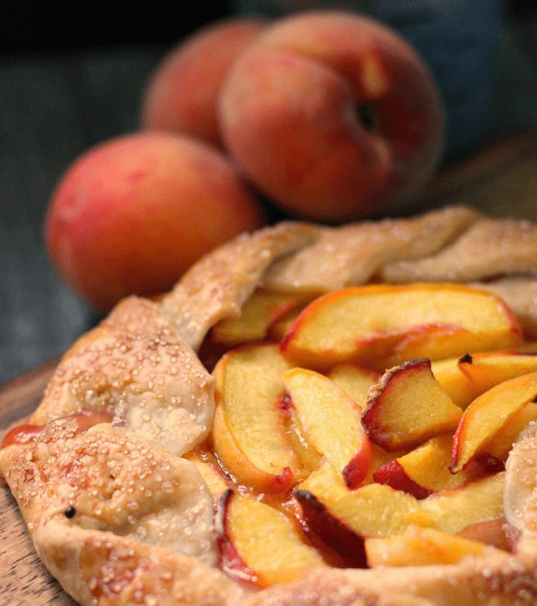 peach galette recipe ~ pre cut galette with whole peaches in background