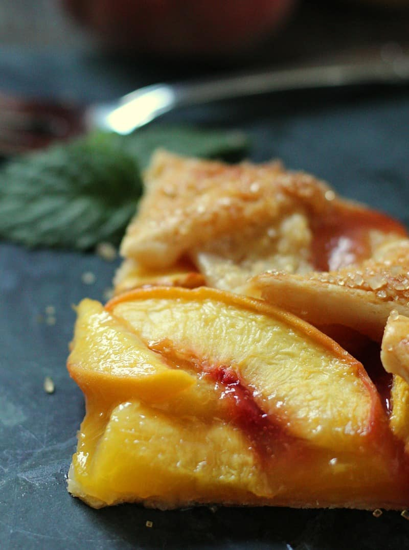 peach galette recipe ~ single slice of peach galette topped with coarse sugar and baked until golden with fresh peaches in the background