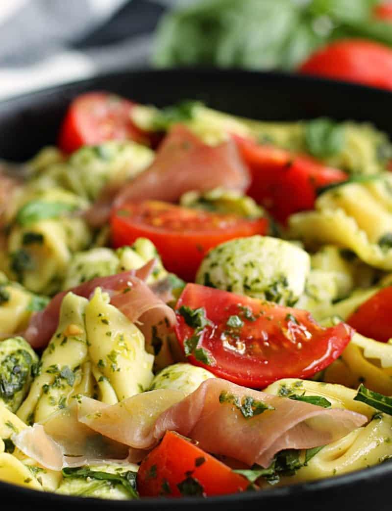 close up pesto tortellini salad with prosciutto