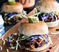 slow cooker beer braised pulled pork ~ side view of slider topped with green and purple shredded cabbage, topped with a pickle.