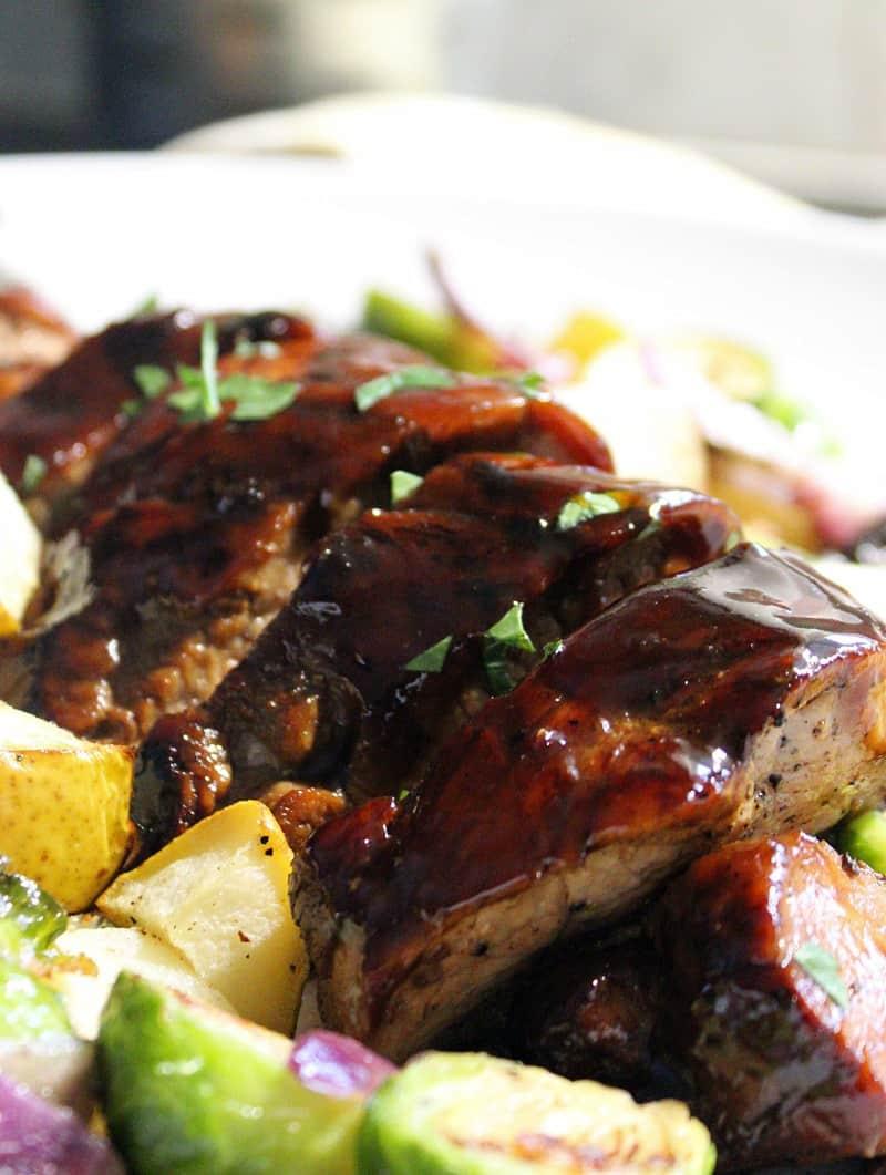 sliced pork roast alongside brussels sprouts, cubed potato medley
