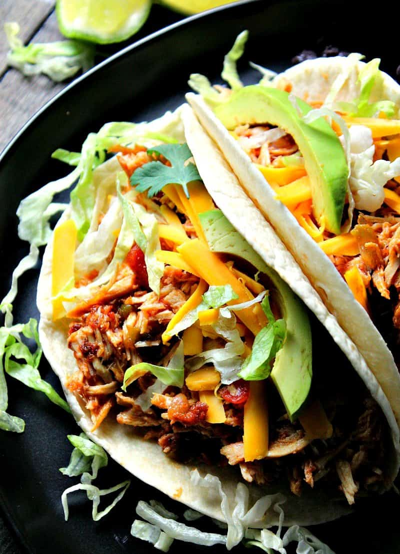 slow cooker salsa chicken ~ 4 ingredients, 5 minute prep for delicious, juicy, bold flavored chicken. Shown in soft shell taco topped with shredded lettuce, tomato, cheddar cheese and sliced avocado.
