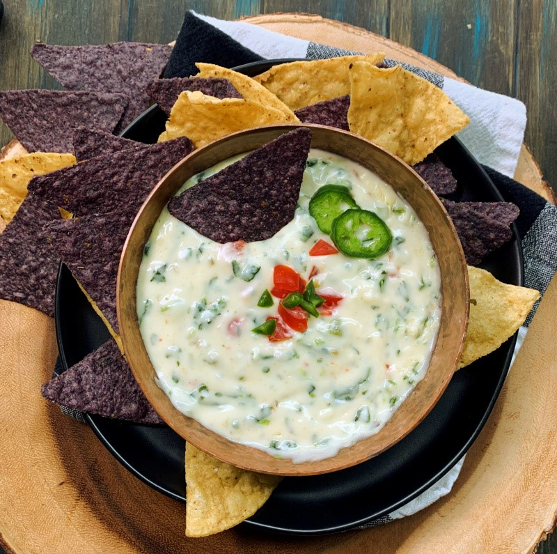 bowl of spinach queso garnished with diced tomatoes and jalapenos