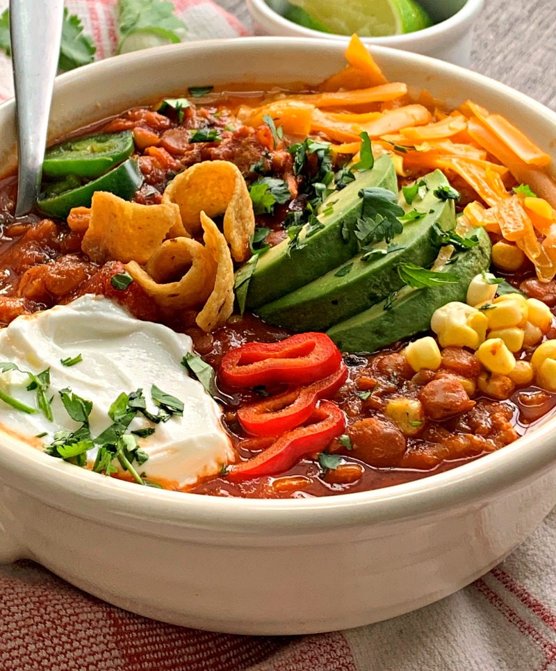 Bowl of turkey lentil chili garnished with cheese, avocado and sour cream