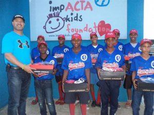 Manny Acta junto a algunos niños beneficiados con regalos a través de su fundación.