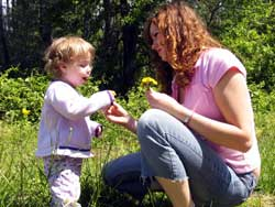 mother sitting with her child and teaching love by offering flowers