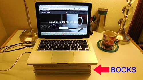 Showing laptop kept over books