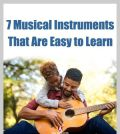 An adult learning musical instrument guitar with kid