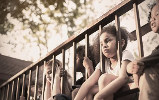 Multicultural little children sitting behind the fence. Homeless