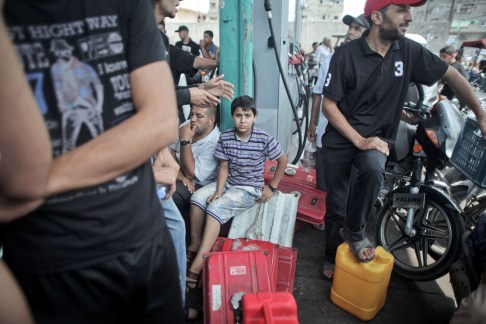 a Palestinian boy waits to fill a container of power generator with fuel from a petrol station in Gaza city, The turmoil in neighboring Egypt has rippled into the Gaza Strip, stranding thousands of people on both sides of the border and causing a painful fuel shortage.