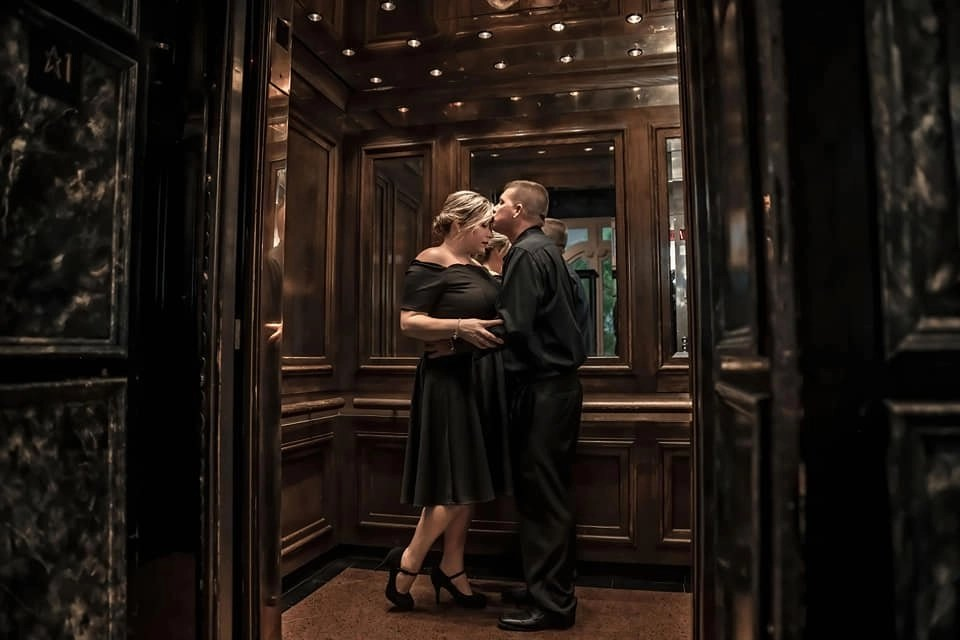 engagement session in elevator with future groom kissing fiance on forehead