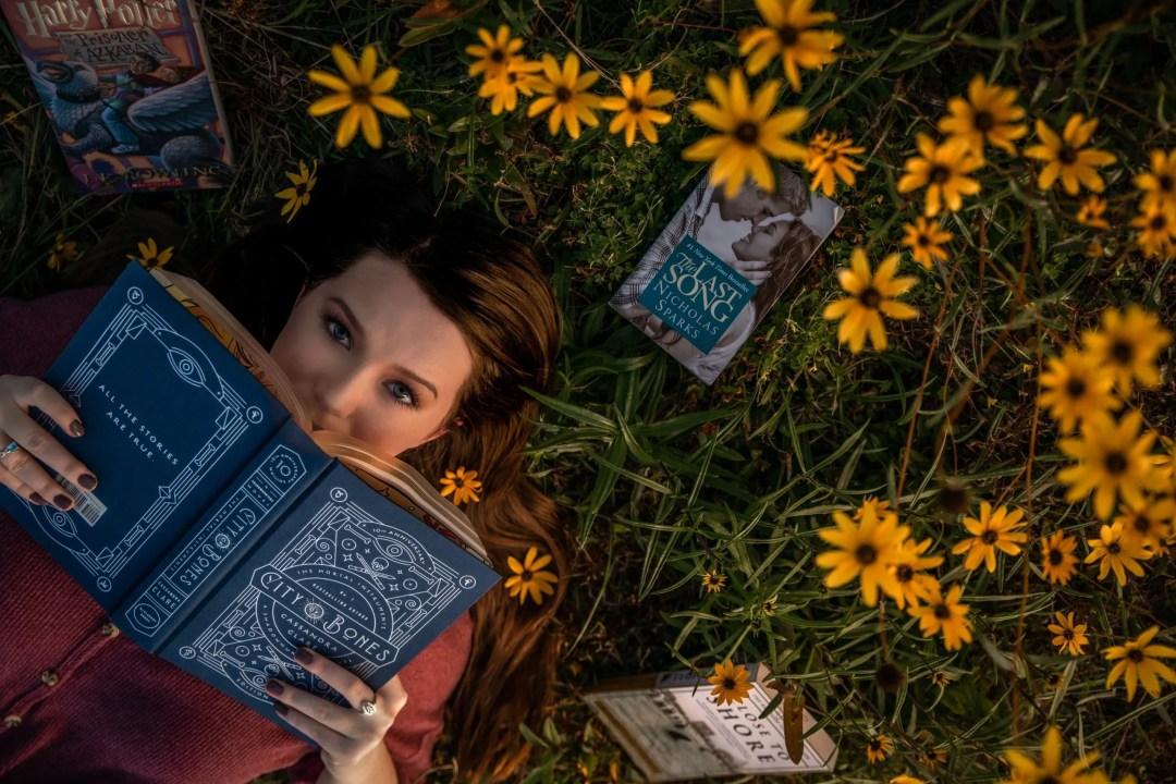 senior portrait reading book in sunflowers