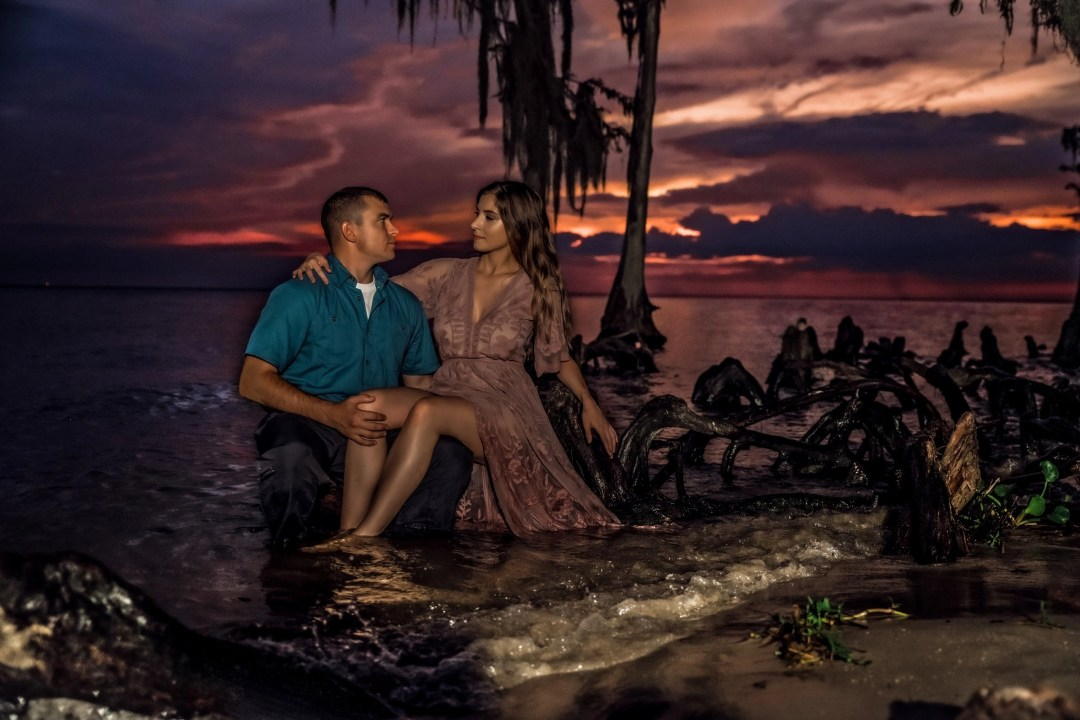 sunset photo of couple in water cypress knees and spanish moss