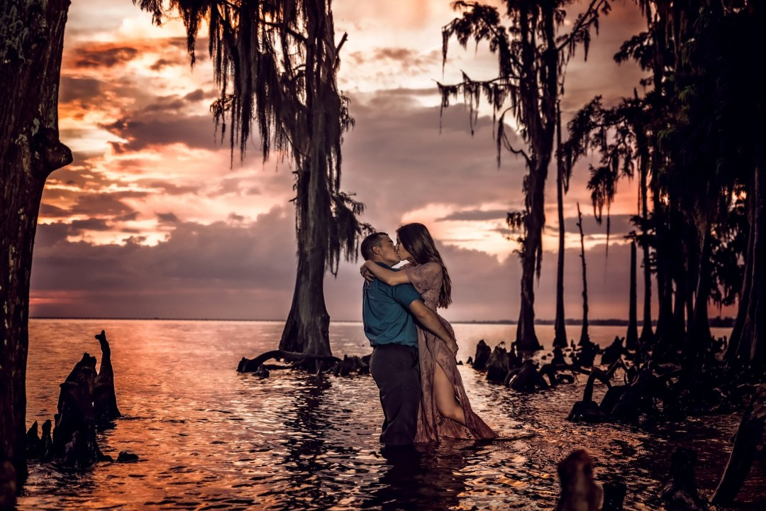 engagement photo shoot of couple kissing in water cypress knees spanish moss