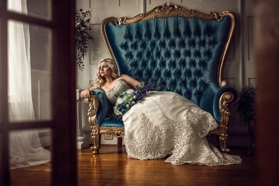 bride in strapless wedding dress on blue and gold chair engagement photos