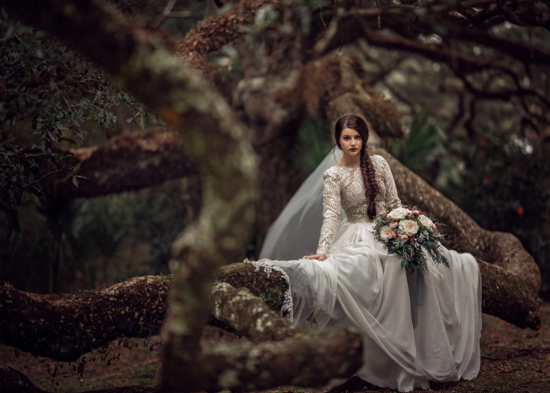 gorgeous brunette bride in long sleeved wedding dress sitting on tree