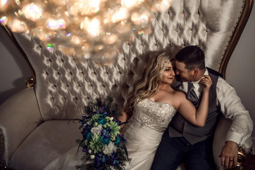 bride holding grooms neck on white chair under chandelier
