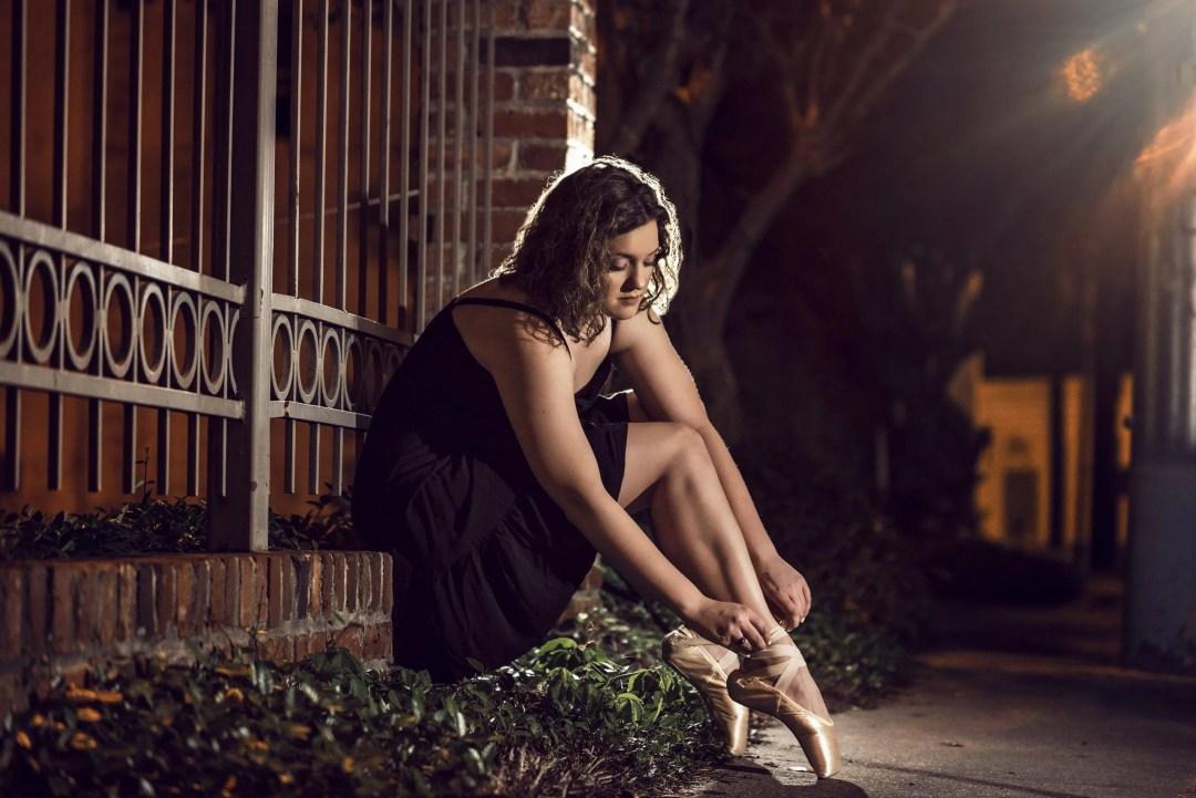 creative unique senior photo female ballet dancer tying toe shoes nighttime