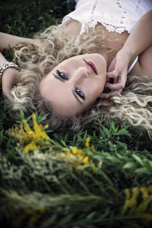 close up headshot blonde senior photo outdoors in grass