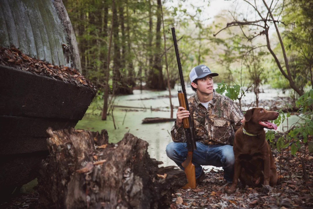 creative senior photo in nature with hunting dog