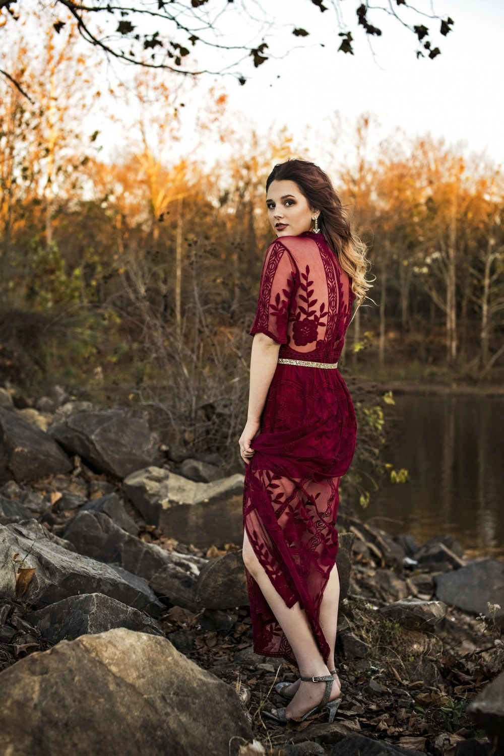 outdoor photography session for senior in red dress by water