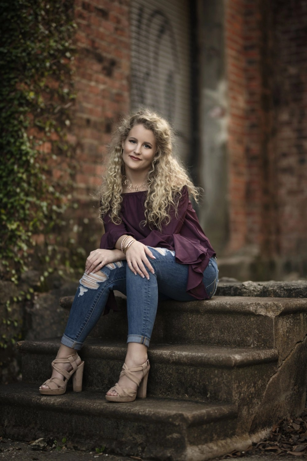 curly haired blonde senior sitting on steps in ripped jeans