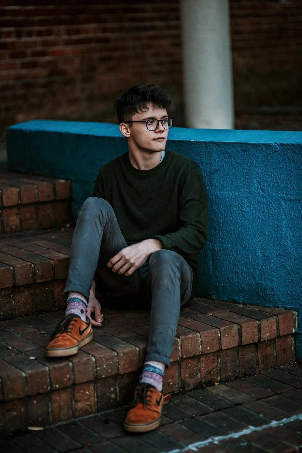 high school senior male on steps near blue wall
