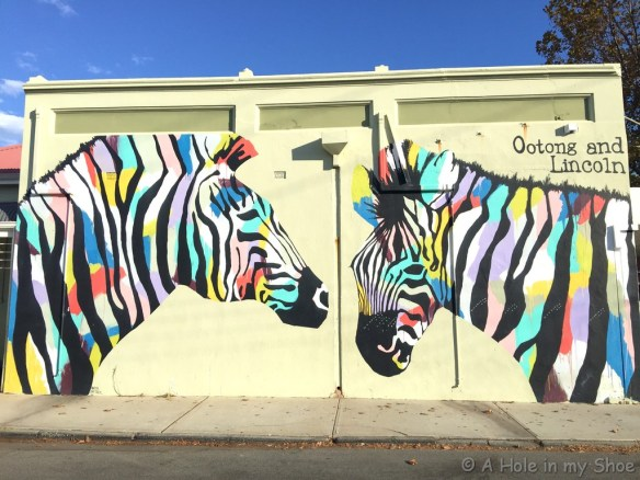 Colourful zebras painted by Anya Brock on the side of Ootong & Lincoln cafe Fremantle