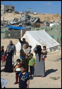 Displaced people in Gaza, with their tents in the rubble