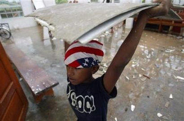 A indigenous Miskito child helps remove debris from the a church damaged Hurricane Felix