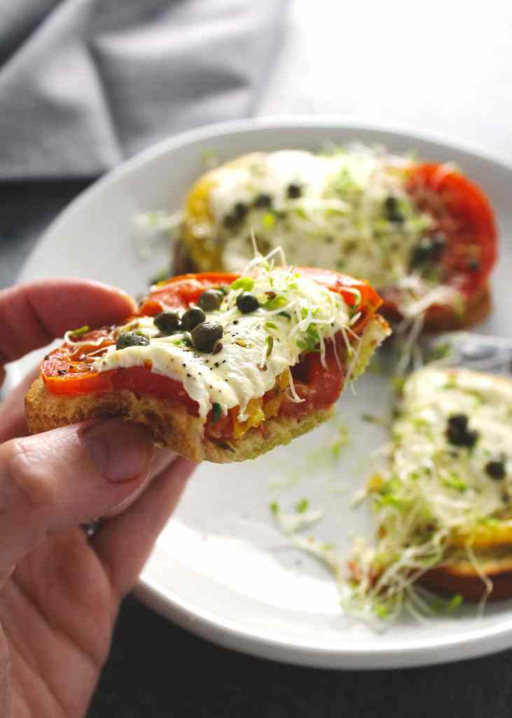 There's something summery about toasted crispy bread drizzled with pesto and topped with melty cheesy covered tomatoes and this tomato sandwich has it all | via @AimeeMarsLiving | #TomatoSandwich #Heirloom