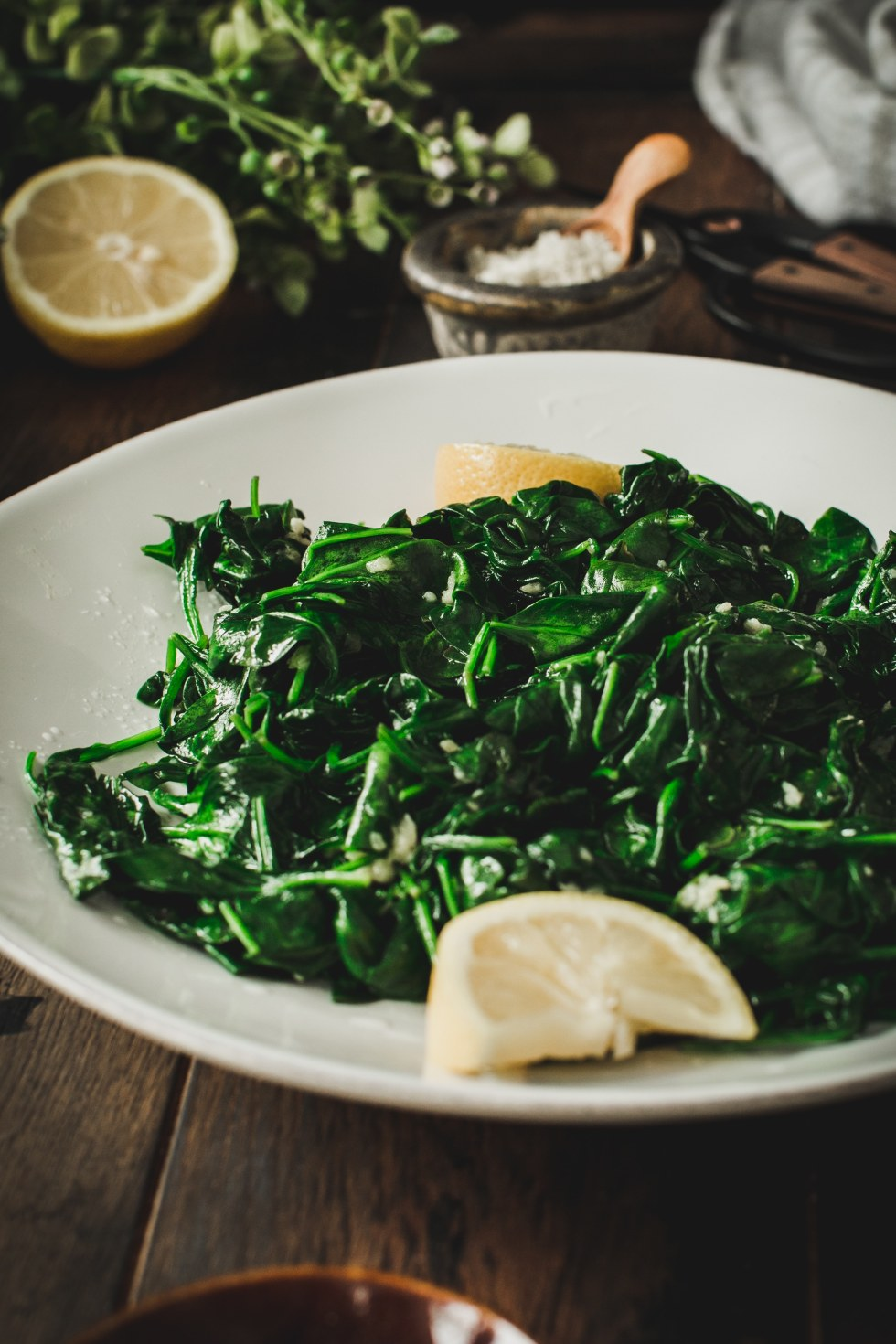 garlic sauteed spinach on white plate with lemons