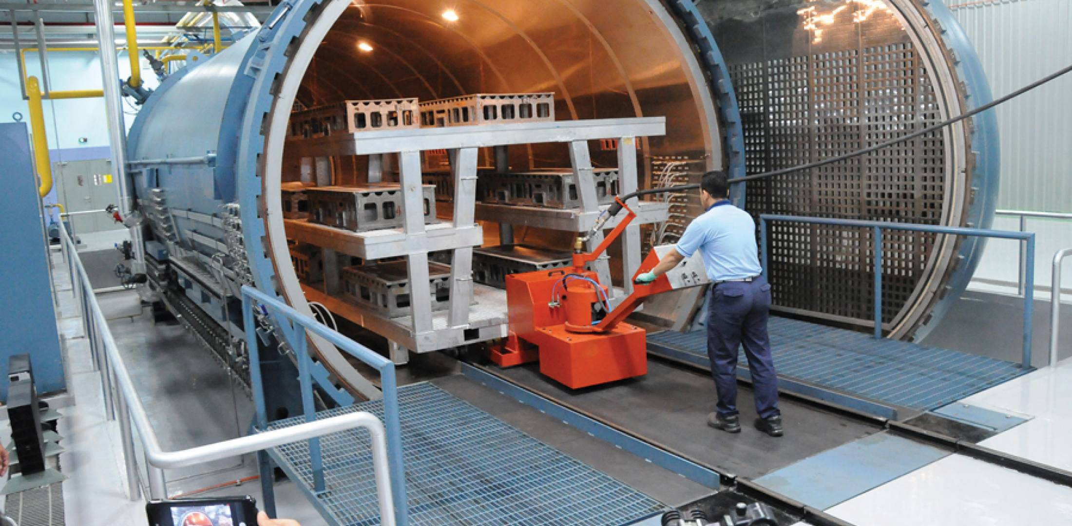 medium resolution of a worker loads aircraft parts into a new autoclave at the expanded aerospace composites malaysia facility