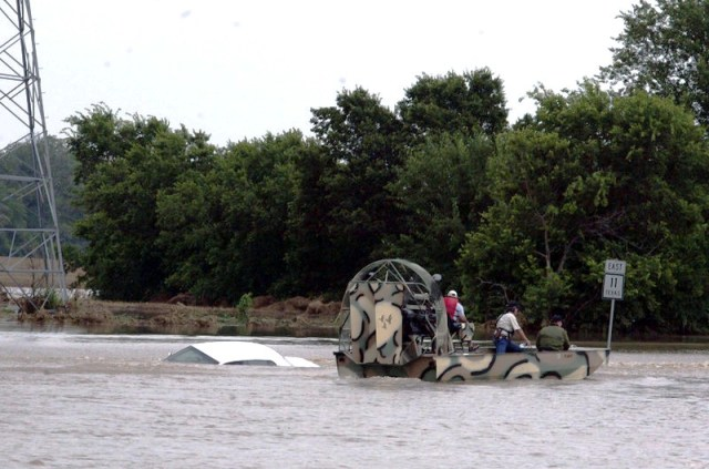 An airboat searches a car that was swept off State Highway 11 in Sherman, Texas photo: Chris Jennings / Herald Democrat