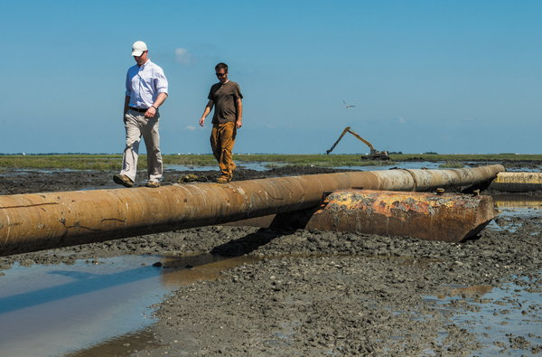 Nick Dilks, left, of Ecosystem Investment Partners, which is funding the work, and Matt Conn, a contractor, inspected a pipeline.