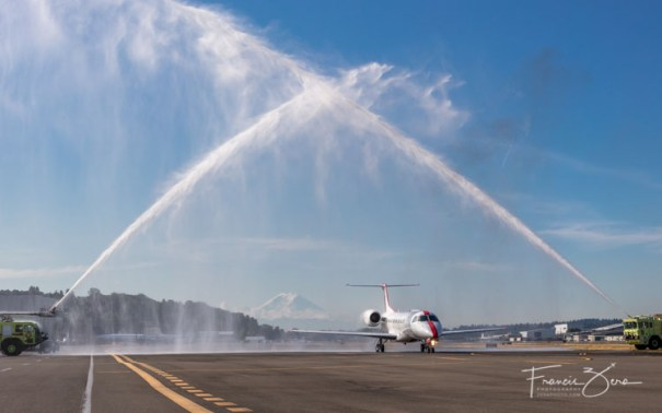 A JetSuiteX ERJ135 getting a water cannon salute at Boeing Field - Mount Rainier provided a dramatic backdrop