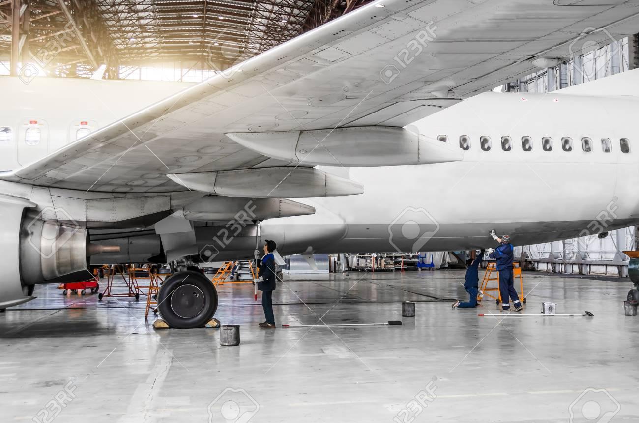 93023737 diverse persone lavano l aereo nell hangar per manutenzione vista del telaio ala e coda Avvitatori per assemblaggio industriale