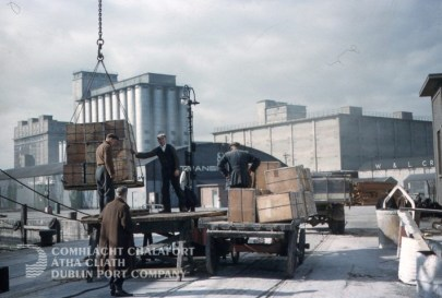 Colour photograph of unloading tea chests onto horse drawn carries, c1960.