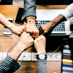 5 business people doing fist bump