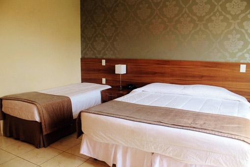 Suite Luxo com uma cama de casal e uma cama de solteiro
